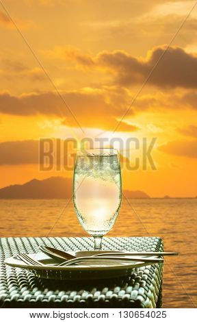 Glass of cold water with sun flare effects, on dining table in sunset