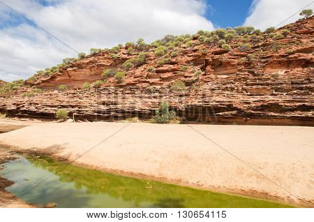 Tumblagooda sandstone cliffs in the valley of the Murchison River gorge with limited water during a drought in Kalbarri National Park with native plants under a blue sky with clouds in Western Australia.