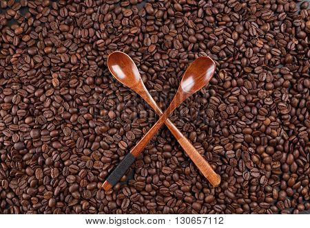 Two Crossed Wooden Spoons On Scattered Coffee Beans