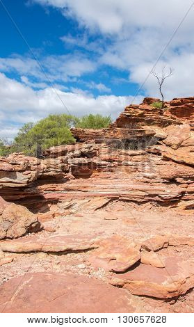 Layers of tumblagooda sandstone in the rocky bluffs of Kalbarri National Park in Western Australia under a blue sky with clouds.