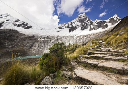 panorama of snow-covered Andes mountains in Peru and blue lake from stone path to punto union pass