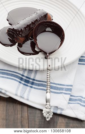 Sweet Chocolate Covered Tube With Silver Spoon On A Plate