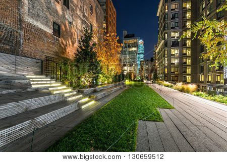 The High Line promenade illuminated in evening surrounded by modern and old buildings in Chelsea. The aerial greenway is also known as Highline or High Line Park. Manhattan, New York CIty