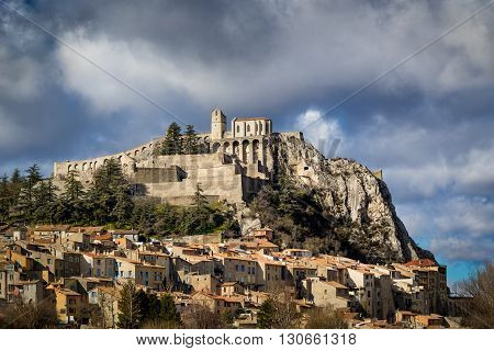 Citadel of Sisteron and rooftops in summer light with clouds. The Sisteron Citadel and its fortifications is located in the Southern Alps (Alpes de Haute Provence) in the Durance Valley. France
