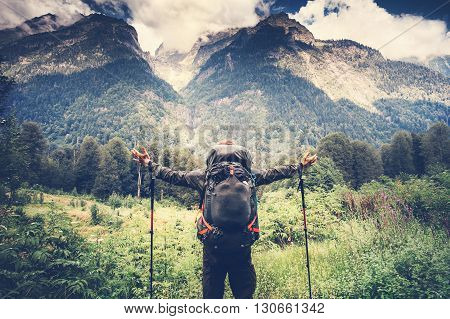 Happy Man with backpack hands raised mountaineering Travel Lifestyle concept beautiful mountains with clouds sky landscape on background adventure vacations outdoor