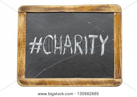 charity hashtag handwritten on vintage school slate board isolated on white