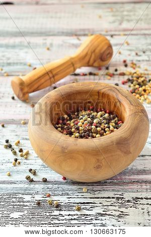 Peppercorns in a mortar on a light wooden table