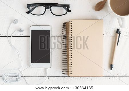 cellphone and earphone with a cup of coffee on white wooden desk Top view