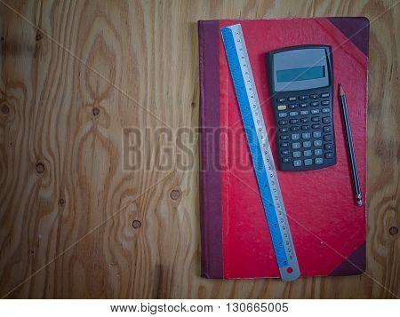 Old red cover notebook and calculator On the wooden floor.