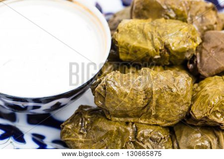 Traditional eastern appetizer dolma stuffed with rice and meat. Served with sour cream sauce and fresh vegetables. Macro. Photo can be used as a whole background.