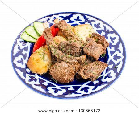 Delicious baked lamb racks with vegetable garnish and minced dill on authentic oriental plate. Isolated on a white background.