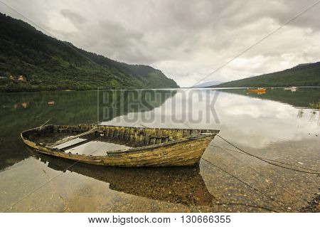 old boat with water in chilean fjord with calm water