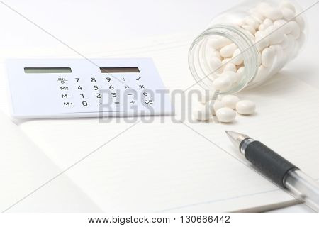 Calculator and white pills spilling out of a transparent medicine bottle.