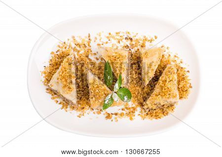 Delicious oriental dessert baklava covered with grated walnuts. Isolated on a white background.