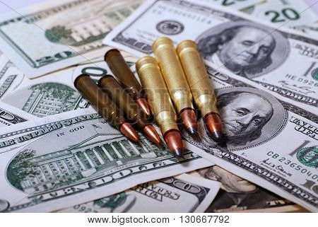 bullets lying on dollar banknotes, selective focus