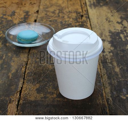 White paper cup of coffee and macaroon on a wooden table