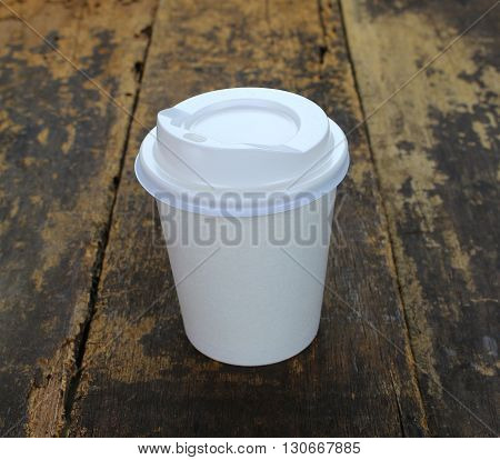 White paper cup of coffee on a wooden table