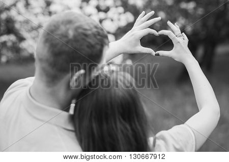 Young couple of man and woman making hearts from hands. Man woman in love. Love concept