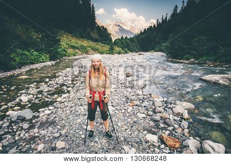Young Woman Traveler with backpack crossing river Travel Lifestyle concept active vacations outdoor forest and mountains wild nature on background