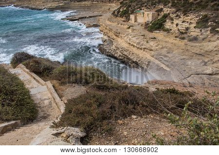 Rocks on the coast of Mediterranean sea south-east of island Malta. Blue water of the sea white waves breaking at the rocks of the island.