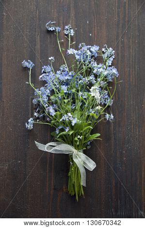 Forget-me-not blue forest flowers bouquet on wooden background