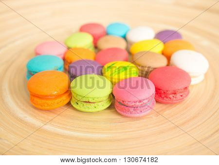 Colorful of mini macaroon on wooden plate background