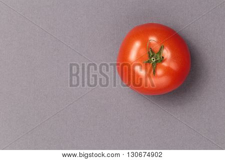 Top view of a red juicy tomato on a grey background. Bright and juicy tomato in the top right corner of the image. Tasty tomato. Tomato wallpaper. Tomato menu. Vegetable texture.