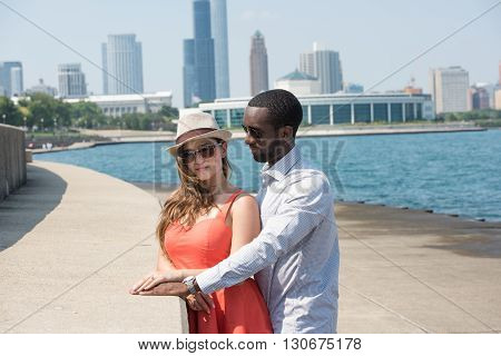 A sweet and affectionate romantic couple spending a joyous and loving time during the day time. On the background, highrise buildings, sky and blue water is seen.