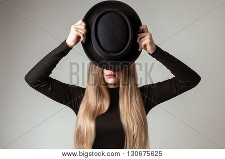 Beautiful long straight blond hair with a black hat in the studio. Woman with red lips is holding in hands