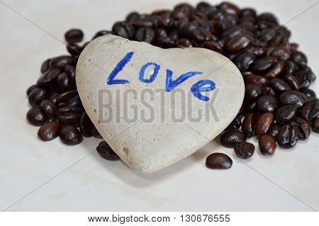 heart rock and coffee bean on tile