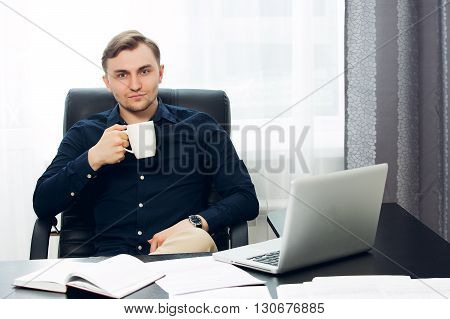 Casual dressed man at the desk looking at the camera