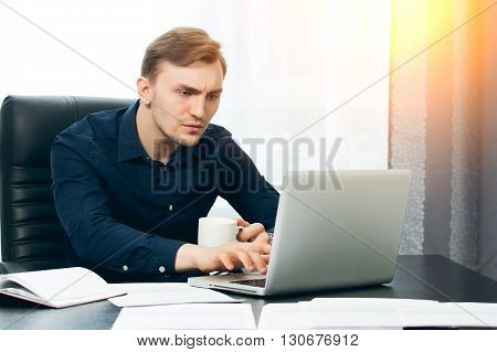 Freelance male journalist writing an article with coffee in hand