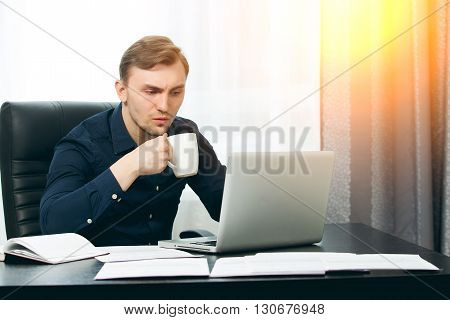 Casual dressed man ready to drink coffee while checking news.