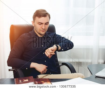 Square picture of businessman looking on his wrist watches.