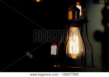 Edison bulb glowing in the dark blurred background