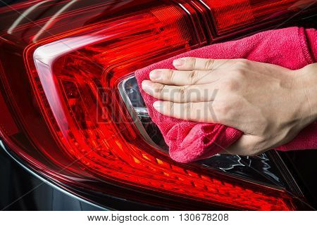 Car detailing series : Closeup of hand cleaning car taillights