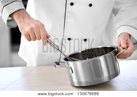 Male hands whisking in a metal pan.