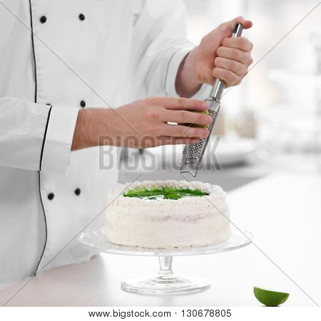 Male hands decorating cake with lime zest