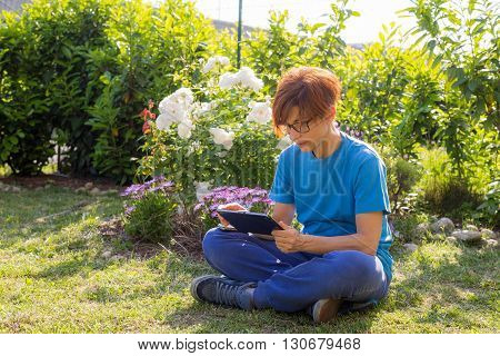 Woman with glasses and casual clothings working with tablet while lying outdoors in flowery garden. Natural daylight real people. Concept of working from everywhere with new connection technology.