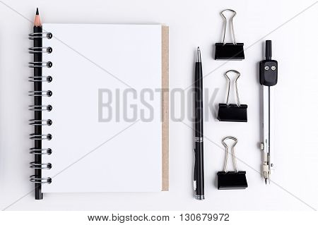 Top view of blank notepad with pencil pen pegs and other items. Mock up
