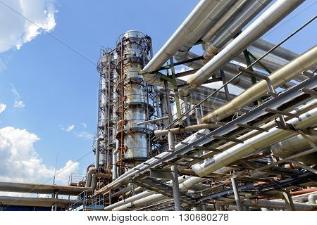 Industrial equipment and pipelines at the gas processing plant on a bright sunny summer day