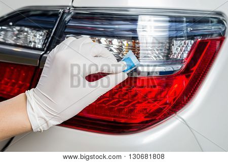 Car detailing series : Closeup of hand coating white car taillights
