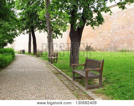 line of wooden benches in the green park in spring and walls of a castle at the background in Brno, Czech Republic