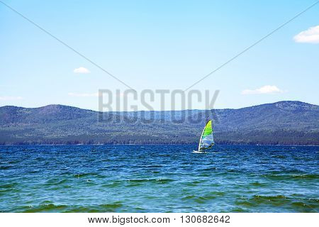 windsurfer on a mountain lake in good weather on a background of blue sky. nature background. windsurfing