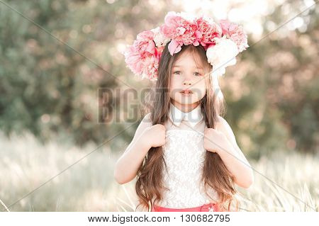Beautiful kid girl 4-5 year old wearing wreath with peony outdoors. Childhood. Looking at camera.
