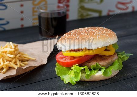Hamburger with tomato pepper and lettuce and french fries