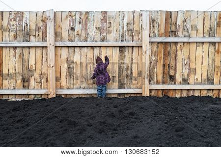 Little girl ploughed field and knocking at the big wooden fence.