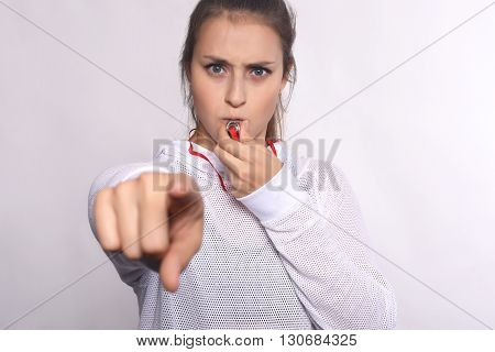 Close up of an athlete young woman with whistle pointing to camera. Isolated white background.