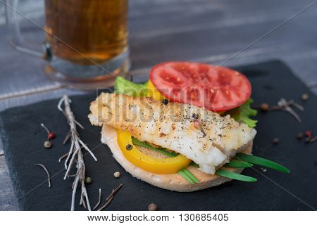 Fish grilled with tomato pepper green onion on the bread on the stone blackboard and mug of beer