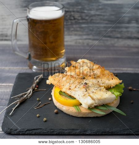 Grilled fish with vegetables on the bread and mug of beer